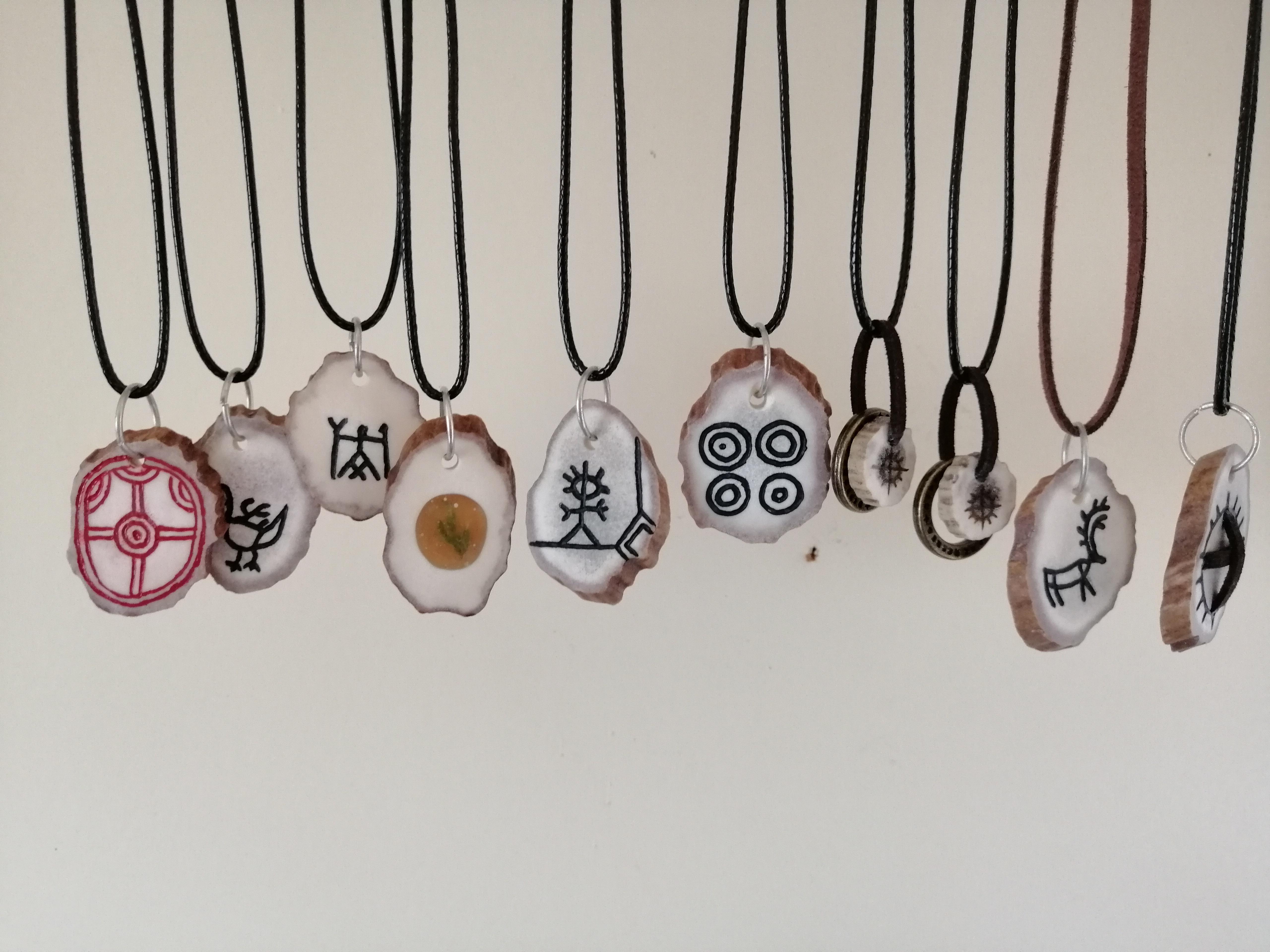 Ni smykker i reinhorn inngraverte figurer hengende fra lærreimer i museumsbutikken på Kokelv Sjøsamiske Museum