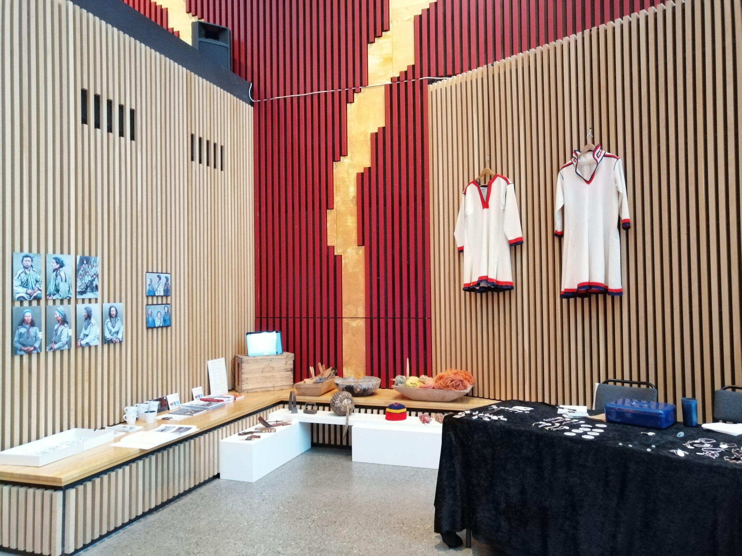 Bilde av Kokelv Sjøsamiske Museum sin pop-up utstilling med to kokelvkofter, litt museumsgjenstander, fotografier og salgsvarer