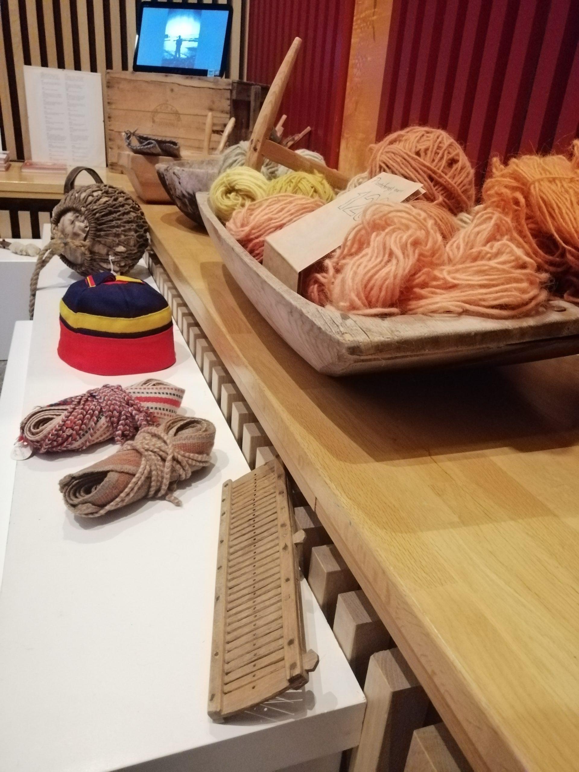 Bilde av museumsgjenstander (to skallebånd, en lue fra Kvalsund, en glasskavel, og et trau av tre med plantefarget garn i orange, brunt og gult