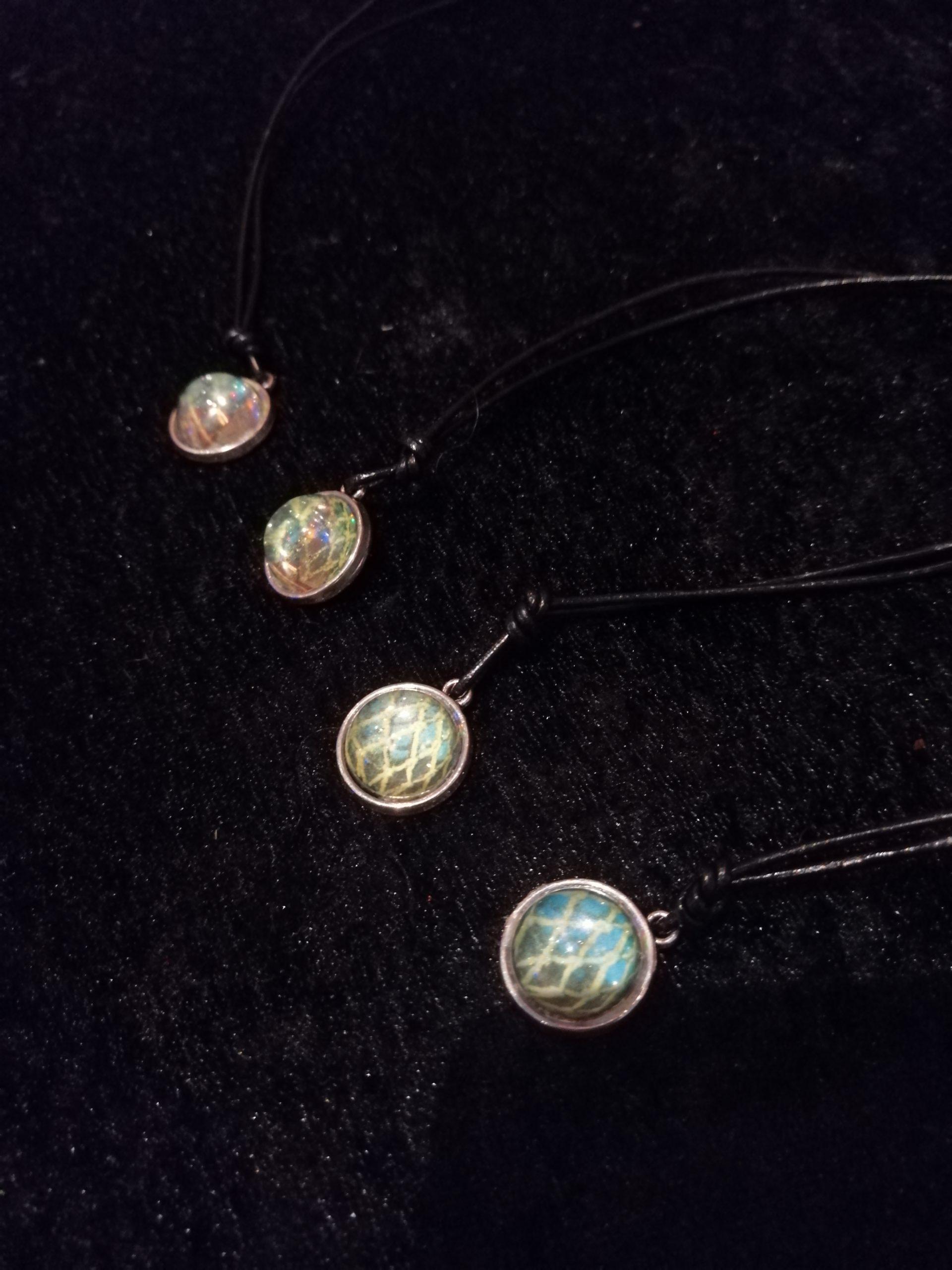 bilde av fire like smykker med glasskavler som motiv