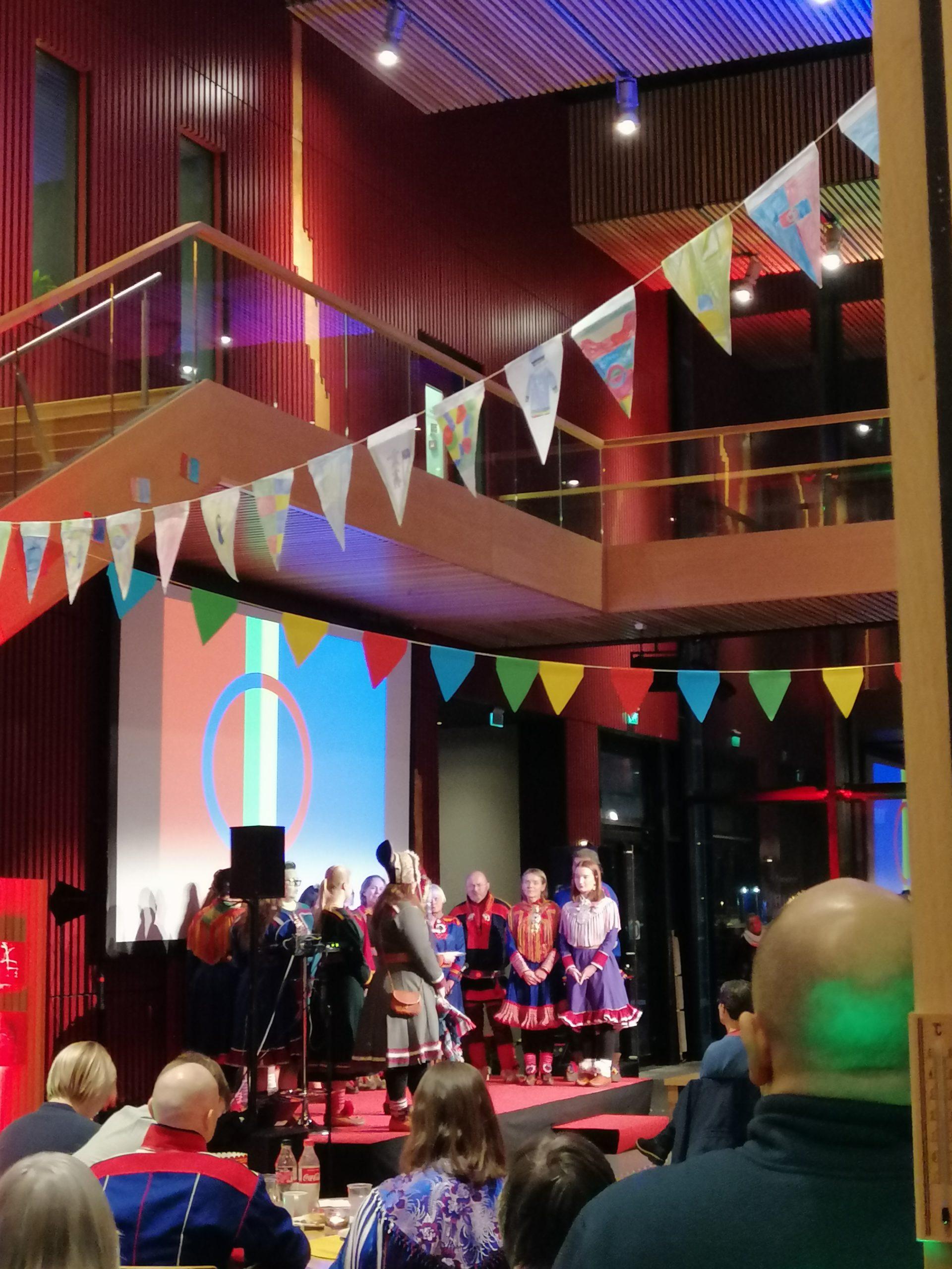 Bilde av scene med flere personer i samiske kofter fra forskjellige områder