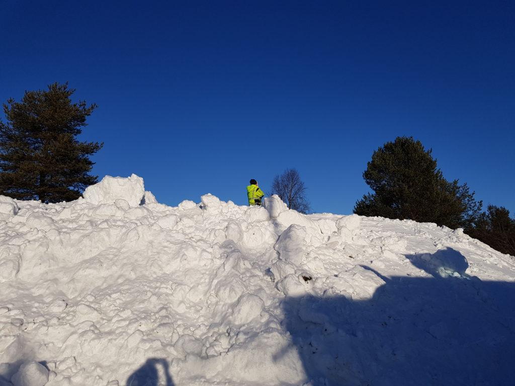 Arbeidsmann på toppen av en stor snehaug