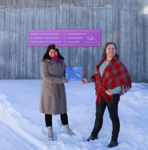 To kvinner viser en blå bok foran De Samiske Samlinger i Karasjok